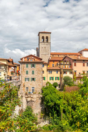 Cividale del Friuli, Italy - Aug 14 2018: View of the old city center with traditional architecture, to the left the Devils bridge spanning the River Natisone and connecting both city parts