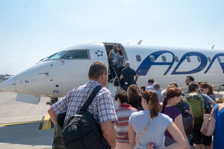 Ljubljana, Slovenia - August 25 2018: Passengers board Adria Airways Bombardier CRJ-900 passenger jet at Ljubljana Airport to SKopje. Adria is local carrier connecting short flights to the Balkans. 에디토리얼