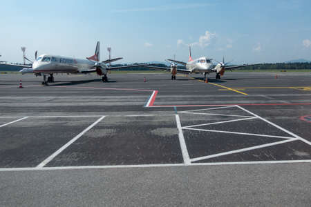 Brnik, Slovenia - August 23 2018: Remains of Darvin Air SA flying as Adria Airways Switzerland. Two SAAB 2000 aircraft on tarmac are left after company declared bancrupcy.