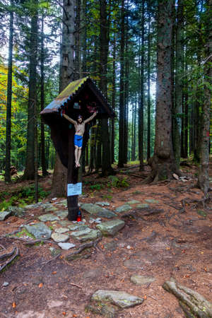 Statue of Jesus on cross in woods, remembrance site on Pohorje near Black Lake, Crno jezero, Urskin kriz