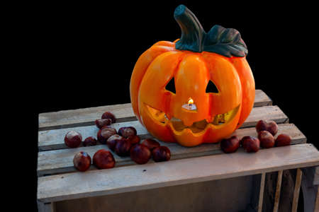 Halloween Pumpkin with Chestnuts Decoration on wooden box, autumn holiday concept,, burning candle seen through nose, candle flickering in wind, isolated on black
