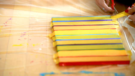 Female artist painting a rainbow with acrylic colors on canvas, hoe made art, DIY tutorial, colorful, mask taping painting for gold guilding