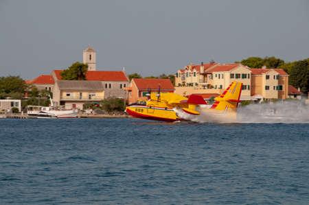Sibenik, Croatia - August 05 2012: Water bomber n action fighting fires near Sibenik. Croatias coast is plagued by wildfires in summer and operates a fleet of waterbombers fighting the fires Redactioneel