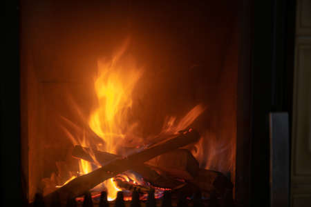 Ecological heating in cold season, fire in stove, close up, firewood in flames burning, detail interior scene, close up
