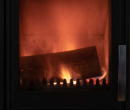 Fire in stove, close up, firewood burning, detail interior scene, winter concept