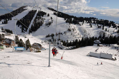 Ski slopes of Alpine wintersport resort Krvavec in Slovenia, people skiing and riding a skilift into the valley