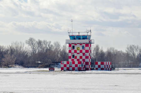 Red and white checkered airport control tower in winter, copyspace, nobody