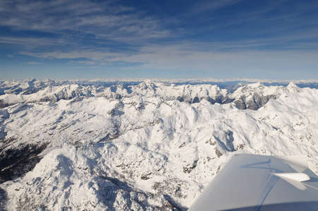 Flying above Mount Triglav in Julian Alps in winter, aerial landscape panorama of mountains covered with snow, highest mountain in Slovenia, Austrian Alps in background