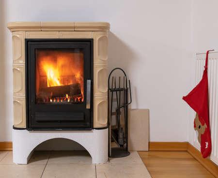 Kachelofen mit Feuer im Inneren, gemütliche und warme Innenszene, Heizung im Winter, Weihnachtsdekoration an der Wand