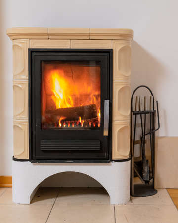 Tiled stove with fire burning inside, cosy and warm interior scene, heating in winter, Christmas decoration on the wall