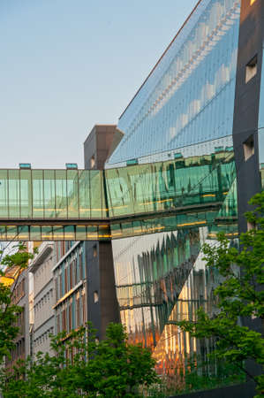 Modern urban architecture, glass and steel construction, sunset and pedestrian bridge reflecting in windows, historic houses in the background, Berlin, Germany Banque d'images - 120368088