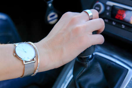 Hand of woman holding gear shifter, manual transmission driving, dashboard in background Banque d'images - 120368092