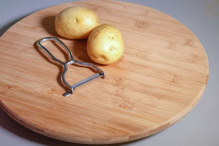 Potatoes on wooden board with a vegetable peeler, close up, isolated Banque d'images - 124691135