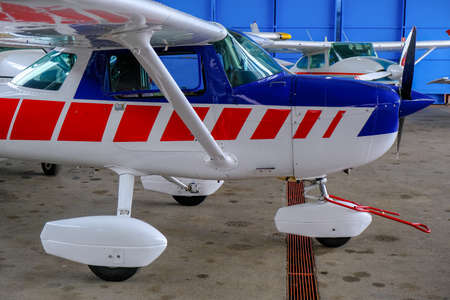 Small sport aircraft in hangar, side view, white, blue and red fuselage Banque d'images - 124691138