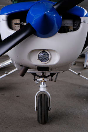 Small sport aircraft in hangar, front view of engine, propeller and nose wheel, aviation and adventure concept Banque d'images - 124691142