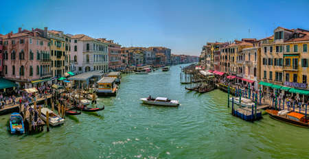 Venice, Italy - April 17 2019: Canale Grande, the Grand Canal in Venice, Italy from the Rialto bridge with gondoals, boats and dense water traffic, tourists walking on shore and sitting in cafes