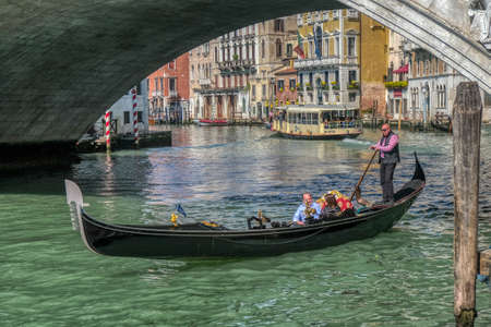 Venice, Italy - April 17 2019: Venetian gondola with tourist couple in Canale Grande, the Grand Canal passing below Rialto bridge