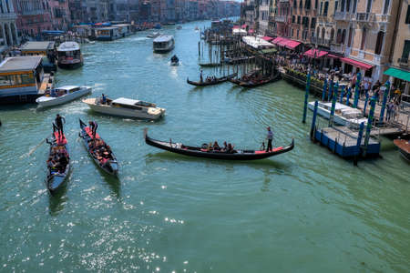 Venice, Italy - April 17 2019: Gondolas and boats in Canale Grande, Grand canal in Venice, one of the most crowded waterways in Venice