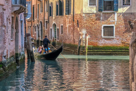 Romantic gondola ride in the canals of Venice, Italy, people unrecognizable Banque d'images - 124691228