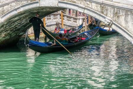 Venice, Italy - April 17 2019: Gondola passing below one of many bridges in Venice, Italy