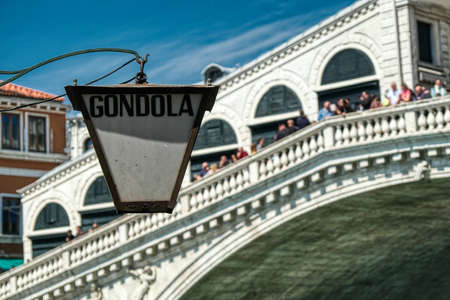 Gondola service lantern with defocused Rialto bridge, full of tourists in background in Venice, Italy Banque d'images - 124692384