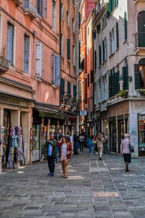 Venice, Italy - April 17 2019: Tourists strolling the streets of Venice with old, historic buildings, shops and cafes