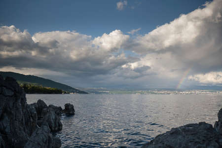 Rainbow in thunderstorm above Croatian coast, storm clouds over Rijeka and Opatija in dusk, calm seas and rocks in front, weather and climate concept