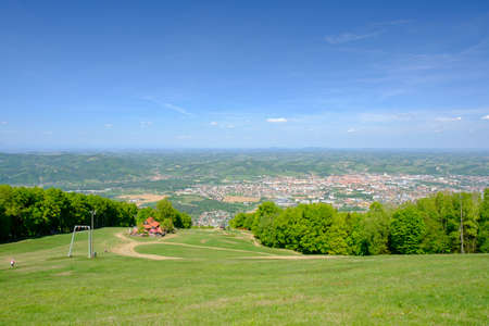 Mariborsko Pohorje, panoramic view of Maribor, Slovenia from Pohorje, mountain hut luka in front, outdoor spring and summer recreation and hiking on ski slopes of Slovenia
