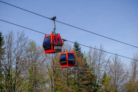 Two red cable cars crossing, overheah cableway on ski slopes and summer adventure park in the european mountains, Pohorje bike park in Maribor, Slovenia