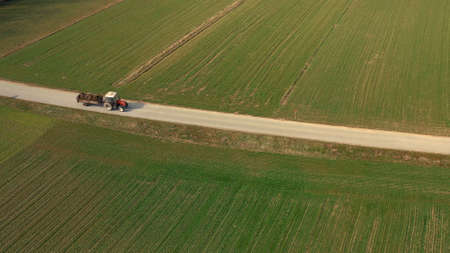 Aerial view of a red tractor and trailer carrying a load of manure on road, agriculture, fertiliying and treating soil