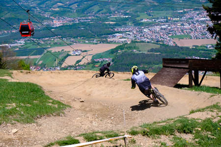 Maribor, Slovenia - May 2, 2019: Downhill mountain bikers riding down the trail on Pohorje near Maribor, Slovenia. Pohorje bike park is very popular with riders.