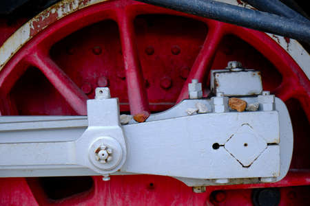 Vintage steam locomotive detail with cranks and red wheels, green bodywork, industrial heritage and transportation