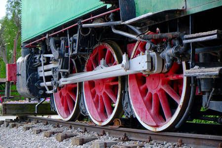 Détail de locomotive à vapeur vintage avec manivelles et roues rouges, carrosserie verte, patrimoine industriel et transport