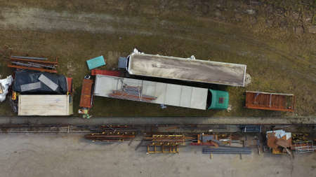 Scrap machinery and trucks on yard, top down aerial view
