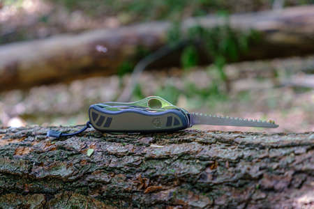Maribor, Slovenia - May 18 2019: Victorinox Swiss Soldiers Knife Model 08, standard army issue model with extended saw blade on tree trunk in forest, iluustrative editorial