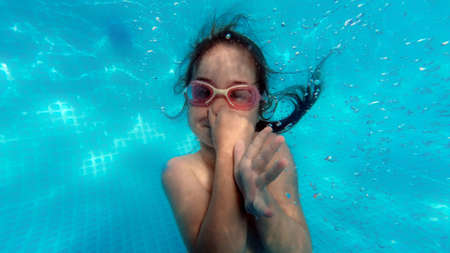 Little girl swimming underwater in pool, child having fun in summer, wearing swimm goggles, caucasian, happyness and childhood