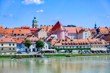 Maribor, Slovenia - June 16, 2019: Lent district in Maribor, Slovenia, a popular waterfront promenade with historical buildings and the oldest grape vine in Europe Редакционное