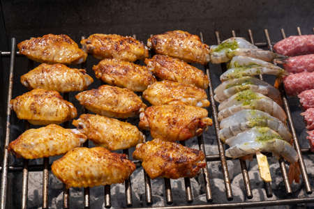 Mixed assortment of marinated meat, chicken, and prawns grilling on hot coals on a BBQ, summer outdoor party, delicious meal preparation