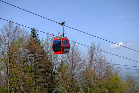 Red cable car cabin against trees and blue sky, mountain transportation and cargo