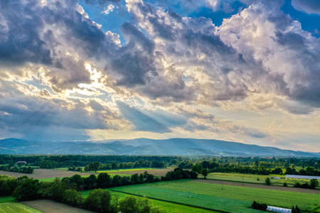 Dramatic clouds above rural landscape, sun rays through clouds, hedges and pastures, tranquil scene, countryside in Slovenia Zdjęcie Seryjne