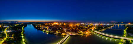 Castle on top of hill at night, aerial view of Ptuj, Slovenia in dusk, wide panorama of historic town on a river in Europe, oldest town in Slovenia