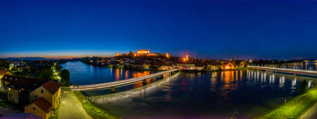Castle on top of hill at night, aerial view of Ptuj, Slovenia in dusk, illuminated bridge across a river, reflection in the water, ancient Roman old town