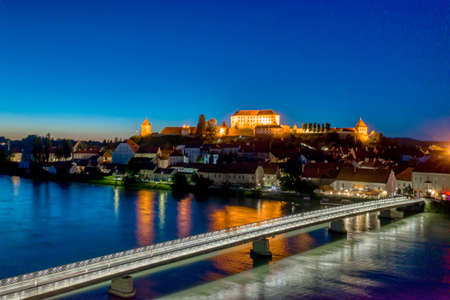 Panoramic view of Castle on top of hill at night, aerial view of Ptuj, Slovenia in dusk with illuminated foot bridge across the Drava river, skyline of medieval town Zdjęcie Seryjne