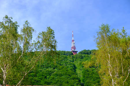 Communications and broadcast tower on top of mountain, red and white antenna on top of forrested slope, Boc in Slovenia