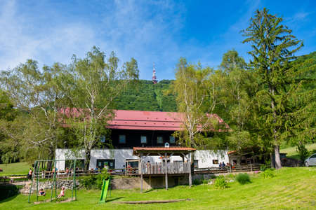 Poljcane, Slovenia - June 09 2019: Mountain hut on Boc near Poljcane, Slovenia, with mountain top and radio antenna in the background, a popular hiking destination in eastern Slovenia