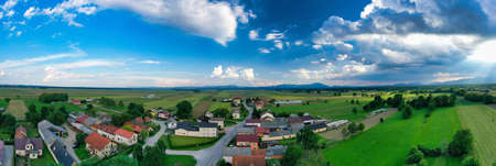 European countryside from the air, village in pannonian plain, Dravsko polje, Slovenia, rural landscape and traditional small villages with houses along the road, village of Podova, Slovenia