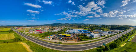 Slovenska Bistrica, Slovenia - June 9 2019: Business and industrial zone in small town in rural Europen landscape and mountains in background, Slovenska Bistrica, Slovenia