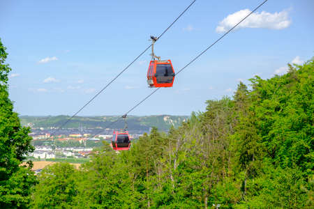 Maribor, Slovenia - May 2 2019: Red cabins of the Pohorska vzpenjaca cable car in Maribor, Slovenia connect the top of Pohorje mountain with the city