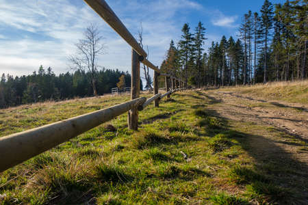 Hiking trail in mountains with wooden fence along the path, autumn nature, alpine mountain landscape, tranquil countryside Stockfoto