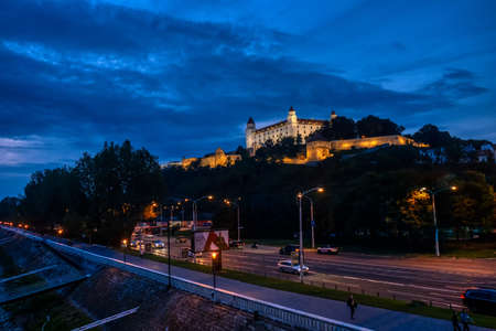 Bratislava, Slovakia - Sept 24 2019: Bratislava castle illuminated in evening glow against dramatic sky, moody and romantic scene of landmark in Slovak capital Editöryel
